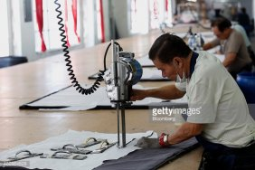 Employees cut fabric at the